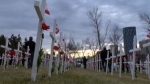 Calgarians pay their respects in the field of crosses near the Centre Street Bridge