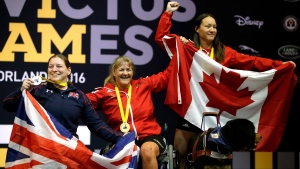Winners in the women's heavyweight powerlift competition, from left, silver medalist Nerys Pearce, of United Kingdom, gold medalist Canada's Christine Gauthier, of Canada, and bronze medalist Natacha Dupuis, of Canada celebrate at the awards ceremony during the Invictus Games, Monday, May 9, 2016, in Kissimmee, Fla. (AP / John Raoux)