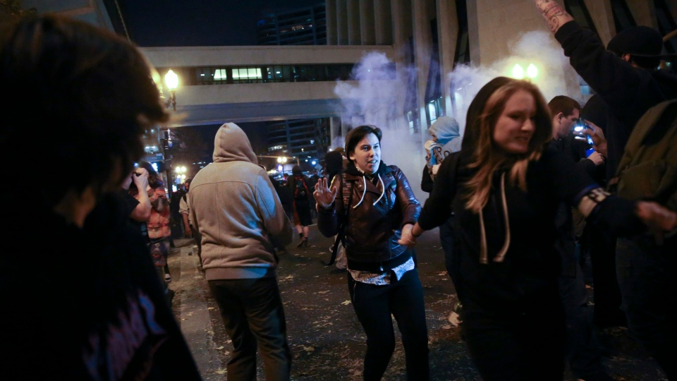 In Portland, police used tear gas and flash-bang grenades Friday to try to disperse the crowd after hundreds of people marched through the city, disrupting traffic and spray-painting graffiti. (Stephanie Yao Long/The Oregonian via AP)