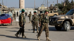 Afghanistan's National Army soldiers guard, blocking the main road to the Bagram Airfield's main gate in Bagram, north of Kabul, Afghanistan, Saturday, Nov. 12, 2016. (AP Photos/Massoud Hossaini)