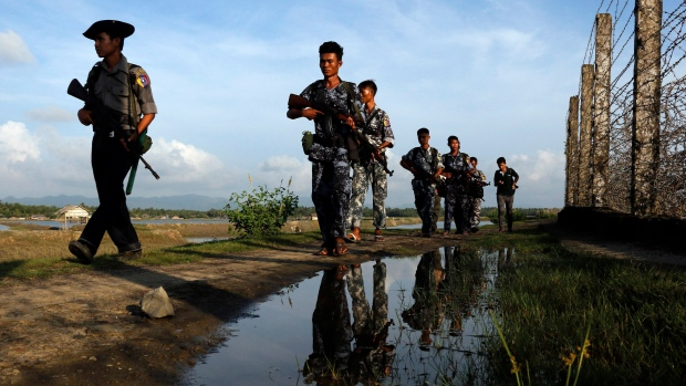 In this Friday, Oct. 14, 2016 file photo, Burma police officers patrol along the border fence between Burma and Bangladesh in Maungdaw, Rakhine State, Burma. (Thein Zaw, File/AP Photo)