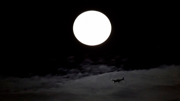 "A small airplane flies with the supermoon behind as it begins to rise in Mississauga, Ont., on Sunday, Sept. 27, 2015. The rising ""supermoon"" will be eclipsed later on in the evening. (THE CANADIAN PRESS/Nathan Denette)"