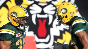 Edmonton Eskimos running back John White (30) celebrates one of his touchdowns with teammate Edmonton Eskimos cornerback Garry Peters (34), in Hamilton, Ont., on Nov. 13, 2016. (Peter Power / THE CANADIAN PRESS)