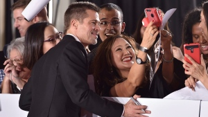 Brad Pitt takes a selfie with a fan at the Los Angeles premiere of 'Allied' on Nov. 9, 2016. (Jordan Strauss / Invision / AP)