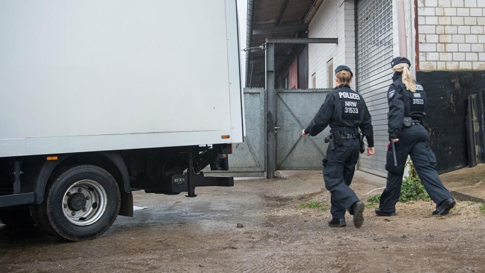 "Police officers walk into a storage facility of the ""Lies! Verlag Gesellschaft"" in Pulheim near Cologne, western Germany, Tuesday, Nov. 15, 2016. (Wolfram Kastl/dpa via AP)"