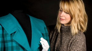 """In this photo provided by Historic Royal Palaces, a conservator handles a pale pink Emanuel blouse with large bow worn by Princess Diana for a portrait by Lord Snowdon in 1981. Kensington Palace says a new exhibition tracing the evolution of the late Princess Diana's style is set to open in February. The palace said Tuesday, Nov. 15, 2016 that the exhibition, """"Diana: Her Fashion Story,"""" will follow from the ruffled blouses in her first appearances to her later life. It's the first palace exhibition in a decade to focus solely on the princess. (Historic Royal Palaces via AP)"""