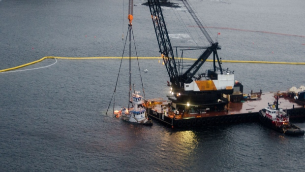 A tug boat that ran aground and sank, releasing thousands of litres of fuel into the water, has been hauled from the ocean floor. The tug will be drained on a barge and then shipped to Vancouver. (Photos from Kyle Artelle)