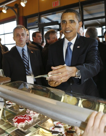 U.S. President Barack Obama tries to pay for some Canadian Maple Leaf cookies, seen in display case, below, as he makes an unannounced visit to a market in Ottawa,  Thursday, Feb. 19, 2009. (AP / Charles Dharapak)