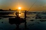 In this Nov. 11, 2016 photo, fishermen throw their fishing rods from Chivo beach as the sun sets in Havana, Cuba.  (AP Photo/Ramon Espinosa)