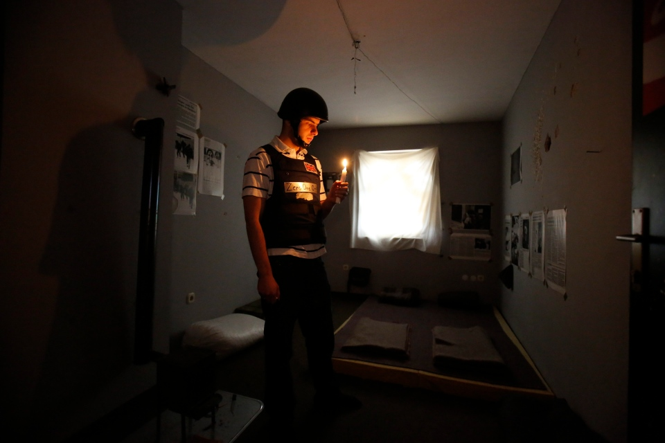 In this Nov. 12, 2016 photo, Bosnian Arian Kurbasic, the owner of the War Hostel in Sarajevo stands with a lit candle in his hand in one of the sparsely furnished hostel rooms. (AP Photo/Amel Emric)