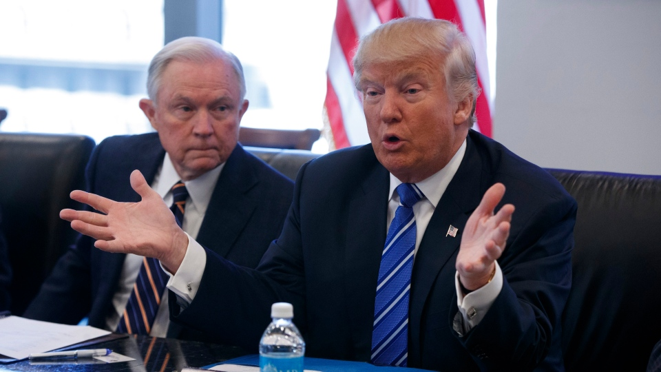 Sen. Jeff Sessions, R-Ala. listens at left as then-Republican presidential candidate Donald Trump speaks during a national security meeting with advisers at Trump Tower in New York on Oct. 7, 2016. (Evan Vucci / AP)