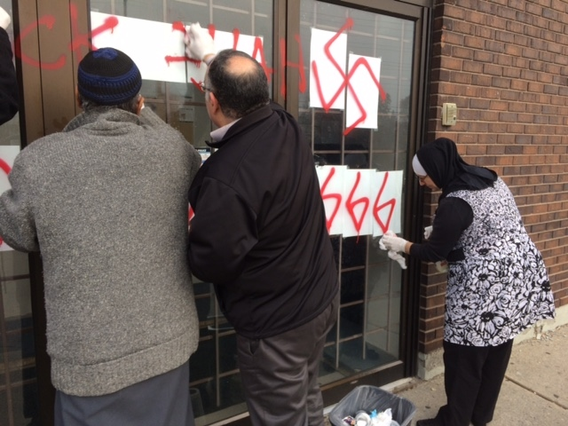 Community members clean up the hate graffiti that appeared overnight Thursday, Nov. 17, 2016 on the doors of an Ottawa Mosque on Northwestern Avenue. (JimO'Grady/CTV Ottawa)
