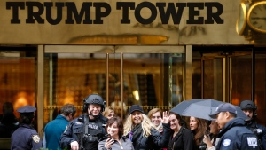 In this Nov. 15, 2016 file photo, a passersby stops for a selfie with a heavily-armed New York City police officer at the main, Fifth Avenue entrance to Trump Tower in New York. (Kathy Willens/AP Photo, File)