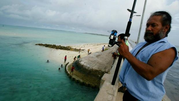 In this March 30, 2004, file photo, a man fishes on a bridge on Tarawa atoll, Kiribati. (AP / Richard Voge, File)