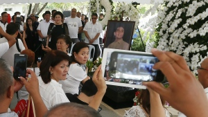 Imelda Marcos, the widow of the late Philippine dictator Ferdinand Marcos, top left in black, addresses hundreds of followers after a mass at his graveyard Saturday, Nov. 19, 2016, a day after Marcos was buried at the Heroes' Cemetery in suburban Taguig city, Philippines. (AP / Bullit Marquez)