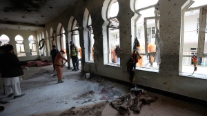 Afghan Municipality workers sweep Baqir-ul Ulom mosque after a suicide attack, in Kabul, Afghanistan, on Nov. 21, 2016. (Rahmat Gul / AP)