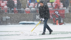 A worker helps to remove snow on the playing field during the CFL eastern final between the Ottawa RedBlacks and Edmonton Eskimos, in Ottawa on Sunday, November 20, 2016. (THE CANADIAN PRESS/Adrian Wyld)