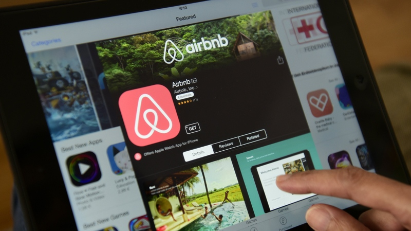 A woman browses the site of U.S. home sharing giant Airbnb on a tablet. (AFP / John Macdougall)