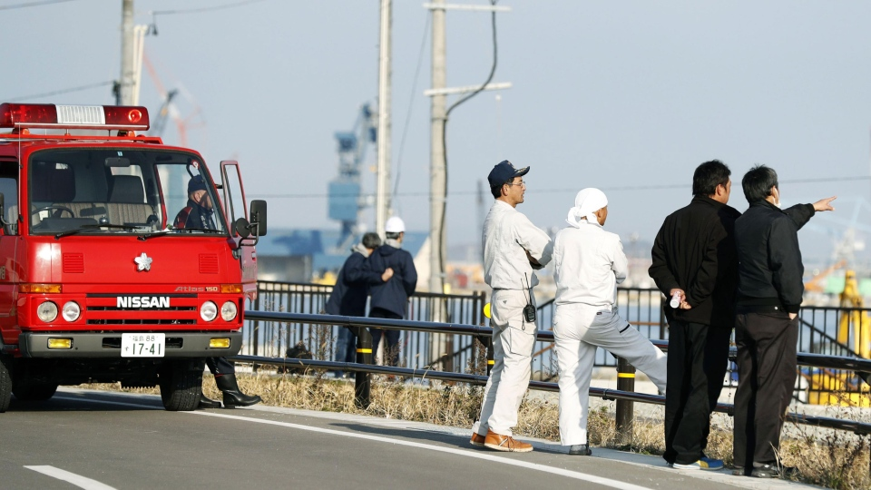 Firefighters and others watch the port to check the water level as a tsunami warning is issued following an earthquake in Soma, Fukushima prefecture, northern Japan, Tuesday, Nov. 22, 2016. (Hironori Asakawa/Kyodo News via AP)