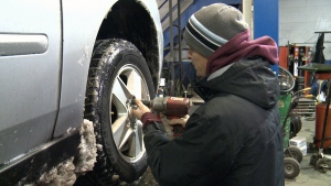 A worker swaps snowy tires for snow tires at Frisby Tire in Nepean, Nov. 21, 2016