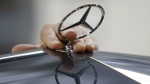 In this July 16, 2009 file photo, an employee of the Daimler AG mounts the Mercedes star on the hood of a car of the Mercedes-Benz E-class on the production line in the Mercedes-Benz site in Sindelfingen, Germany. (AP / Thomas Kienzle, File)