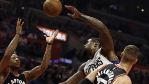 Toronto Raptors guard DeMar DeRozan competes for a rebound with Los Angeles Clippers center DeAndre Jordan, centre, and Toronto Raptors center Jonas Valanciunas watches during the first half of an NBA basketball game in Los Angeles on Monday, Nov. 21, 2016. (AP / Alex Gallardo)