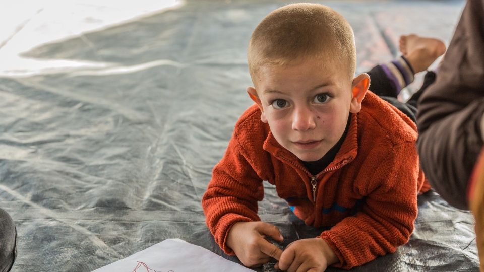 A child from Mosul draws at the Child Friendly Space in the Zelican camp, located 25 kilometres outside of Mosul. (World Vision)