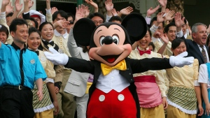 FILE - In this Aug. 9, 2005 file photo, Disney character Mickey Mouse displays a welcoming gesture with other Disney staff members after a press tour of the Hong Kong Disneyland hotel. (Vincent Yu, File/AP Photo)