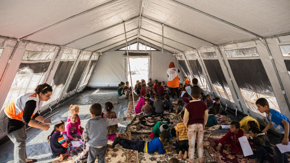 Children play games and draw pictures in the tented space located inside the Zelican camp. (World Vision)