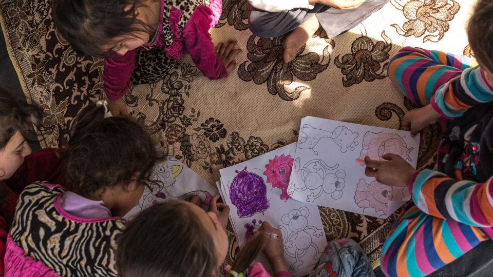 A group of children colouring. (Source: World Vision)