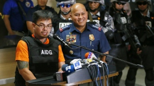 """Alleged Filipino drug lord Kerwin Espinosa, front left, answers questions at a news conference as he is presented to the media by Philippine National Police Chief Gen. Ronald """"Bato"""" Dela Rosa, front right, upon arrival from Abu Dhabi early Friday, Nov. 18, 2016 at Camp Crame in suburban Quezon city, northeast of Manila, Philippines. (AP / Bullit Marquez)"""