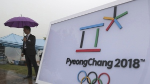 Security personnel stands by a logo of the 2018 PyeongChang Olympic Winter Games before an event to mark the start of the 500-day countdown in Seoul, South Korea, Tuesday, Sept. 27, 2016. (AP / Lee Jin-man)