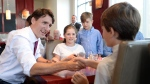Canadian Prime Minister Justin Trudeau shakes hands with Russell Scarrow as Charlotte and James Faragher look on during a visit to a restaurant Wednesday July 20, 2016 in Aylmer, Que. (Adrian Wyld/The Canadian Press)
