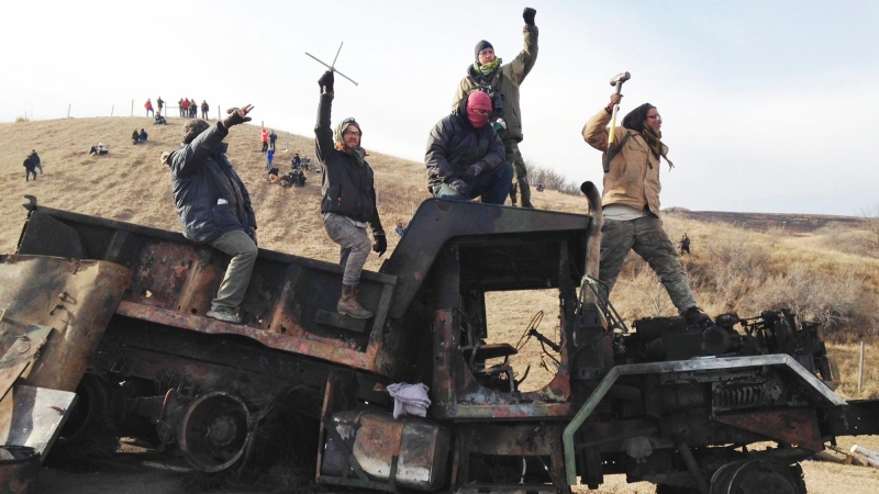 In this file photo, protesters against the Dakota Access oil pipeline stand on a burned-out truck near Cannon Ball, N.D., on Monday, Nov. 21, 2016. (AP / James MacPherson)