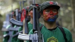 Members of the New People's Army communist rebels with face painted to conceal their identities, march with their firearms before a news conference held at their guerrilla encampment tucked in the harsh wilderness of the Sierra Madre mountains southeast of Manila, Philippines on Nov. 23, 2016. (AP / Aaron Favila)