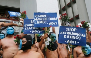 Students belonging to a fraternity at the University of the Philippines, the country's premier state university, display placards as they run naked around the campus to condemn last week's burial of the late Philippine dictator Ferdinand Marcos at the Heroes' Cemetery Friday, Nov. 25, 2016 in suburban Quezon city, northeast of Manila, Philippines. (AP Photo/Bullit Marquez)