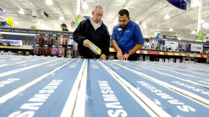 General Manager Sid Uppal (right) helps a customer at Best Buy on Black Friday, in Ottawa on Friday, Nov. 25, 2016. (Justin Tang / THE CANADIAN PRESS)
