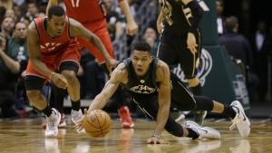 Milwaukee Bucks' Giannis Antetokounmpo, right dives for at the ball against Toronto Raptors' Kyle Lowry during the second half of an NBA basketball game Friday, Nov. 25, 2016, in Milwaukee. (AP / Jeffrey Phelps)