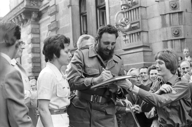 Cuba's leader Fidel Castro autographs a book during his visit to East Berlin in the former German Democratic Republic, June 1972. (Prensa Latina via AP Images/Rogelio More)