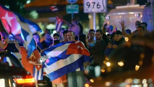 People react to the death of Cuban leader Fidel Castro in Miami, Saturday, Nov. 26, 2016. The death of Castro prompted celebrations among the country's exiles in Miami, and expressions of sorrow from some world leaders. (Michael Laughlin/South Florida Sun-Sentinel via AP)