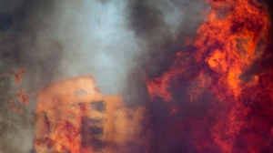 A wildfire rages in Haifa, Israel, Thursday, Nov. 24, 2016. The blaze ripped through parts of Israel's third-largest city, forcing tens of thousands of people to evacuate their homes and prompting a rare call-up of hundreds of military reservists to join overstretched police and firefighters. While there were no serious injuries, several dozen people were hospitalized for smoke inhalation. (AP Photo/Ariel Schalit)