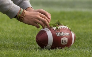 Ottawa Redblacks fullback Brendan Gillanders puts grass on the ball from the natural turf of the BMO field during the Eastern Conference practice, in Toronto on Saturday, November 26, 2016. (Paul Chiasson / THE CANADIAN PRESS)