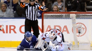 Toronto Maple Leafs' Mitchell Marner, left, crashes into Washington Capitals' Brenden Holtby during the third period of an NHL hockey game in Toronto, Saturday, Nov. 26, 2016. (Jon Blacker/The Canadian Press via AP)