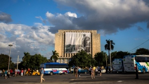 Tourists walk the streets on Revolution Square as workers hang a giant banner with a picture of Cuba's late leader Fidel Castro as a young revolutionary, from the Cuban National Library building in Havana, Cuba, Sunday, Nov. 27, 2016. (AP Photo/Desmond Boylan)