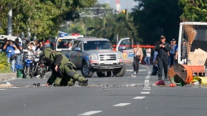 A Philippine National Police bomb disposal squad member, wearing a bomb-proof suit, leans to check the scene shortly after detonating in the middle of a boulevard, a suspicious package believed to be suspected IED or Improvised Explosive Device that was found in the trash bin near the U.S. Embassy in Manila, Philippines, on Monday, Nov. 28, 2016. (AP Photo/Bullit Marquez)