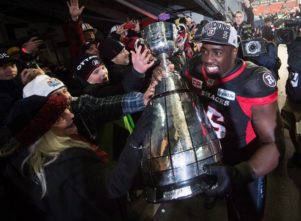 Ottawa Redblacks defensive lineman Moton Hopkins (95) shares the Grey Cup with fans after defeating the Calgary Stampeders in the 104th CFL Grey Cup Sunday, November 27, 2016 in Toronto. THE CANADIAN PRESS/Nathan Denette