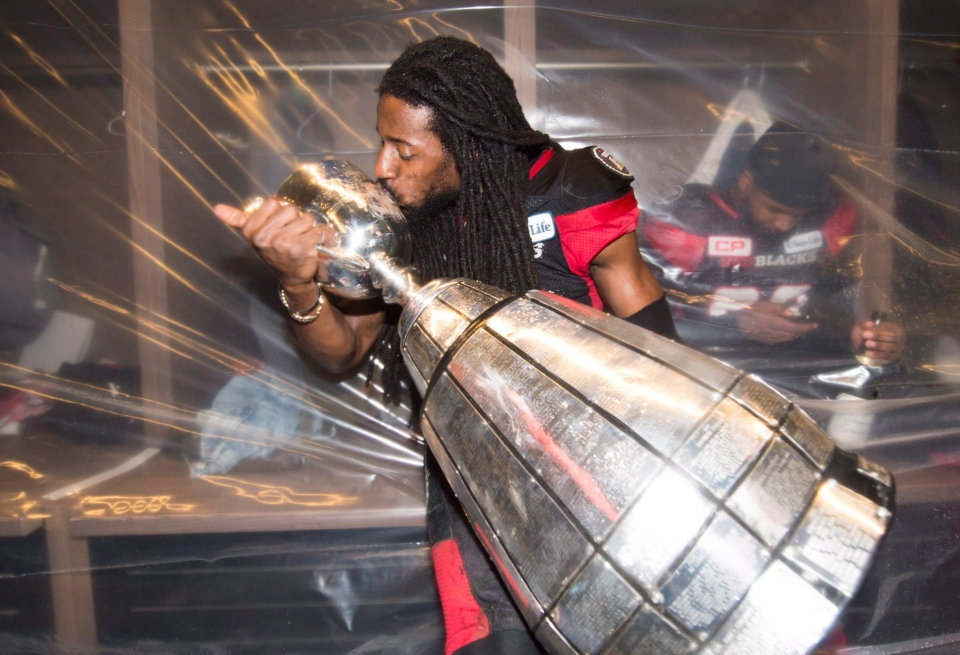 Ottawa Redblacks defensive back Abdul Kanneh (14) kisses the Grey Cup as he celebrates his team's win over the Calgary Stampeders in overtime CFL Grey Cup football action on Sunday, November 28, 2016 in Toronto. THE CANADIAN PRESS/Nathan Denette