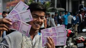 An Indian displays a new Rupees 2000 currency outside a bank in Allahabad, India, on Nov. 13, 2016. (Rajesh Kumar Singh / AP)