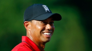 FILE - In this June 26, 2016, file photo, Tiger Woods stands on the 18th green during the trophy ceremony for Quicken Loans National PGA golf tournament winner Billy Hurley III in Bethesda, Md. (AP Photo/Patrick Semansky, File)