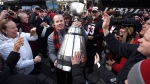 Ottawa Redblacks head coach Rick Campbell carries the Grey Cup as fans reach out to touch the trophy after the team returned to Ottawa, after defeating the Calgary Stampeders, on Monday, Nov. 28, 2016. THE CANADIAN PRESS/Justin Tang